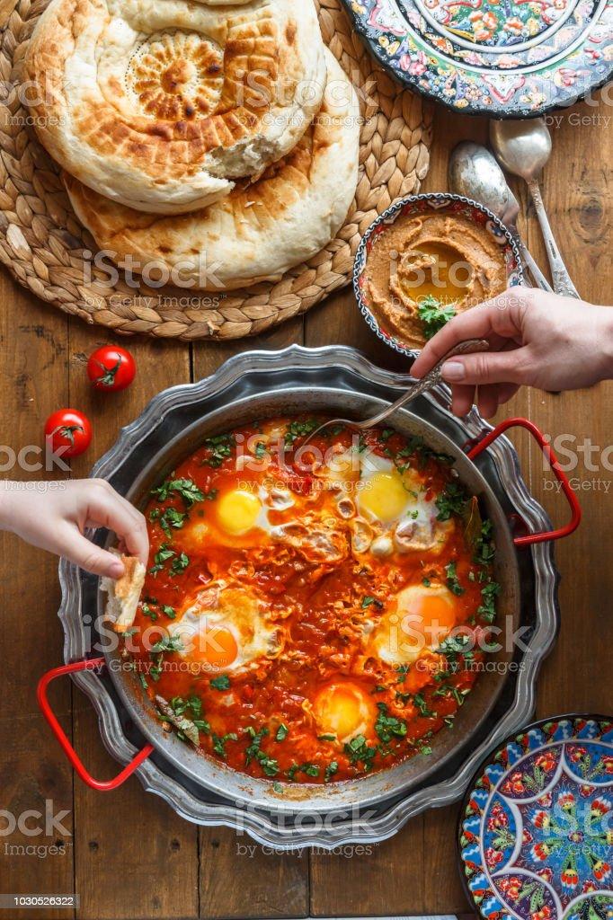 Tasty family breakfast with shakshuka, bread and hummus. Rustic style stock photo