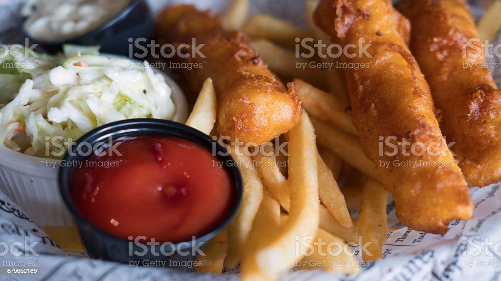 Sabrosos pescado y patatas fritas, ensalada de repollo y salsas servidas en estilo inglés en una placa cubierta con recortes de periódico - foto de stock