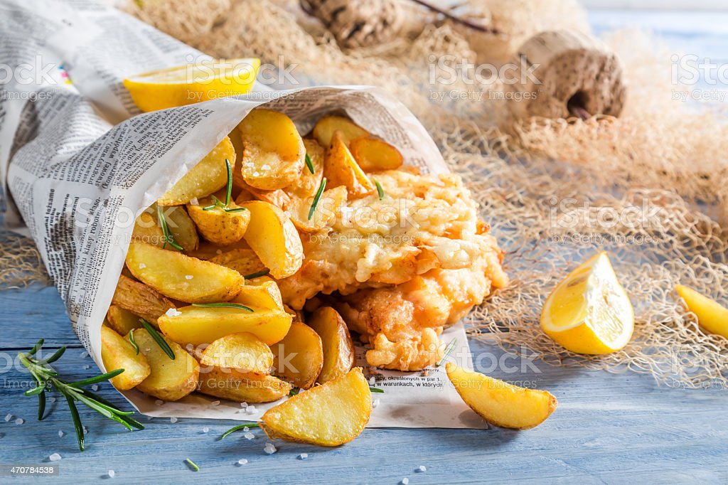 Tasty fish and chips served in paper with lemon stock photo