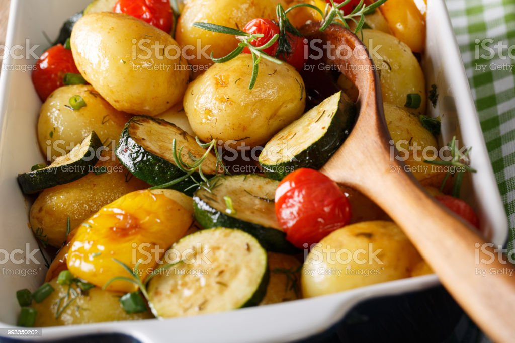 Tasty Food: potatoes baked with zucchini, bell pepper and tomatoes macro in a baking dish. horizontal stock photo