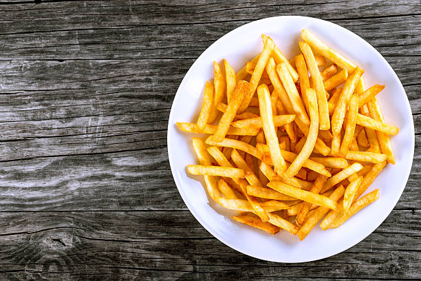 tasty french fries on plate, on wooden table background - friet stockfoto's en -beelden