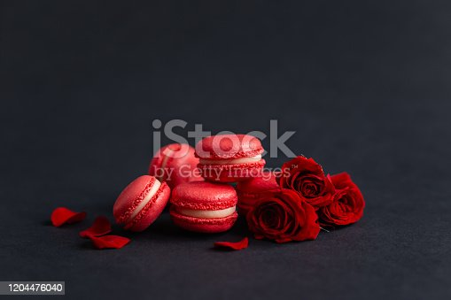 Tasty french macarons with red roses on a black background. Concept for Valentine's day. Place for text.