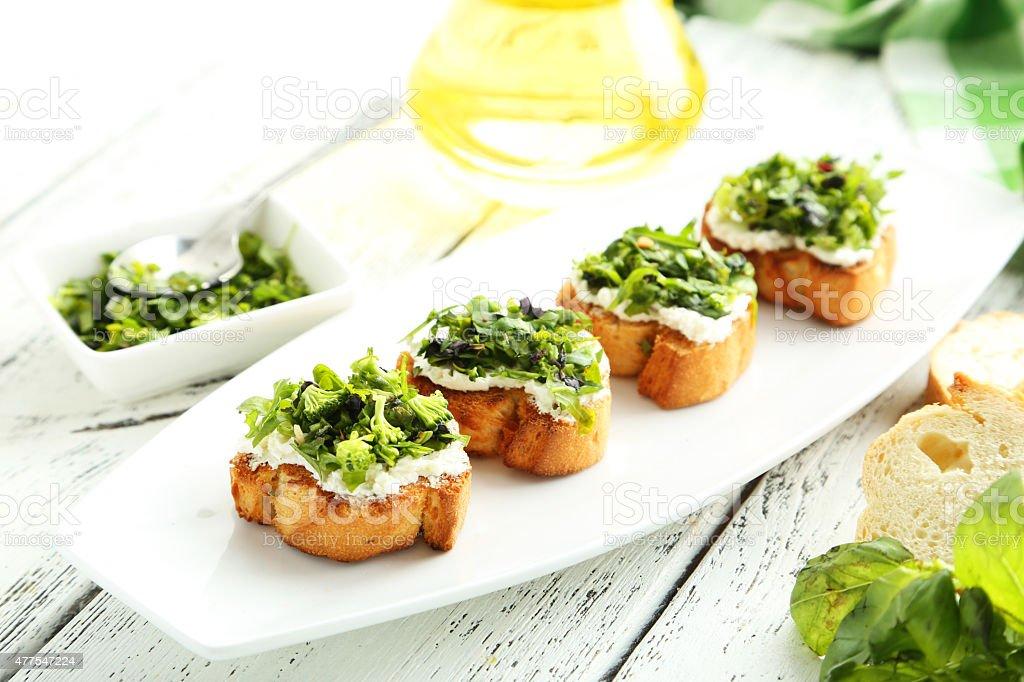 Tasty fresh bruschetta on plate on white wooden background stock photo