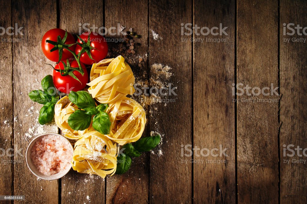 Tasty Fresh Colorful Ingredients for Cooking Pasta Tagliatelle with Fresh Basil and Tomatoes. stock photo