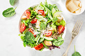 Tasty appetizing fresh salad with chicken, tomatoes, cucumbers and cheese parmesan in bowl on white marble backhground. View from above. Horizontal with copy space.