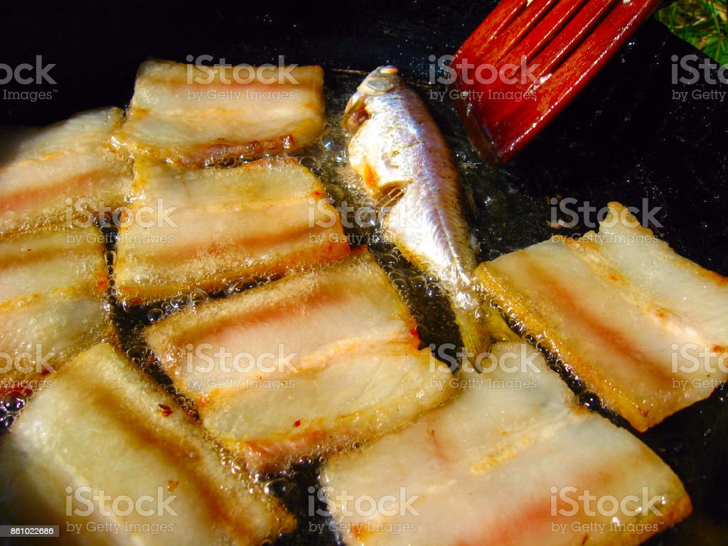 Tasty fried bacon on a frying pan stock photo