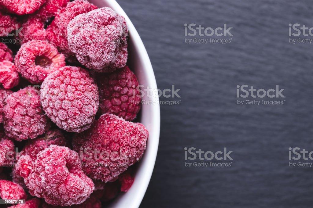 Tasty frozen raspberries in bowl on black textured background. royalty-free stock photo
