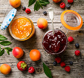 istock Tasty fruit red strawberry berry jams in glass jar with fruits on wooden table. Closeup. Top View. 802061092