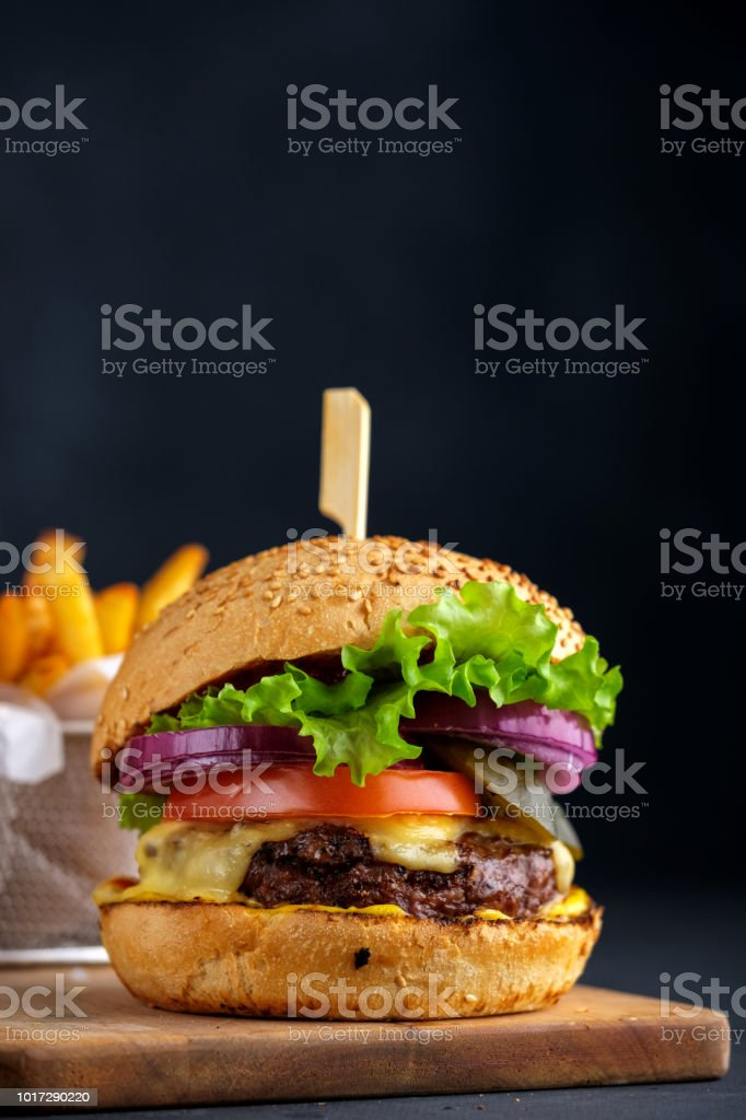 Tasty grilled beef burger with lettuce, cheese and onion served on cutting board on a black wooden table, with copyspace. стоковое фото
