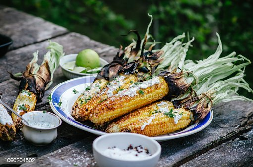 Tasty grilled corn cobs on old table in the open air.