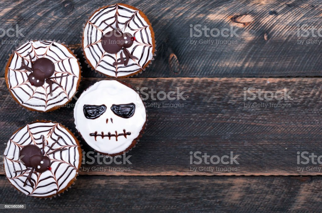 Tasty halloween cupcakes decorated with icing on old wooden background. Halloween sweet background. Lots of copyspace