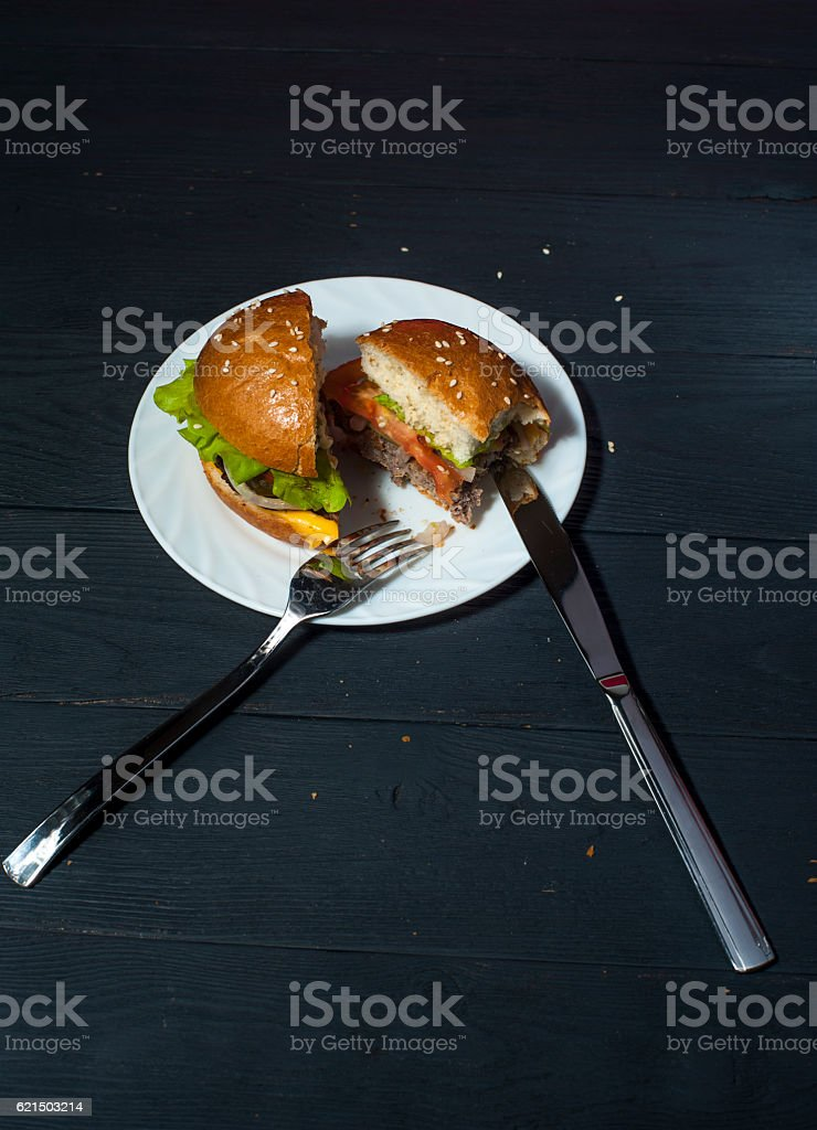 Tasty hamburger on plate with fork and knife foto stock royalty-free