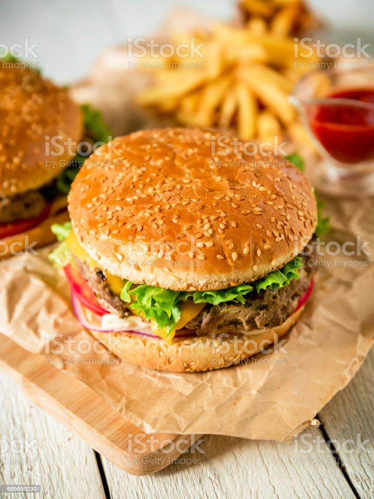맛 있는 햄버거와 쇠고기, 소스와 나무 바탕에 감자 튀김. 플랫이 하다. 최고의 볼 수 있습니다. royalty-free 스톡 사진