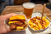Tasty hamburger with french fries with bacon and chesse and beer on wooden table