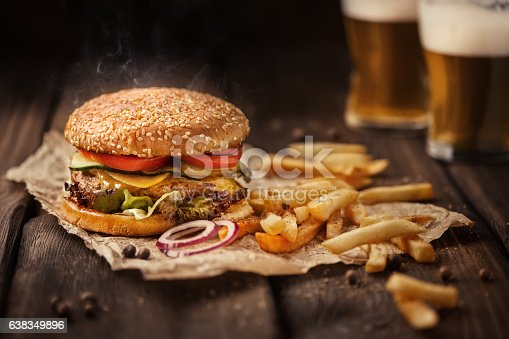 istock Tasty hamburger with french fries and beer on wooden table 638349896
