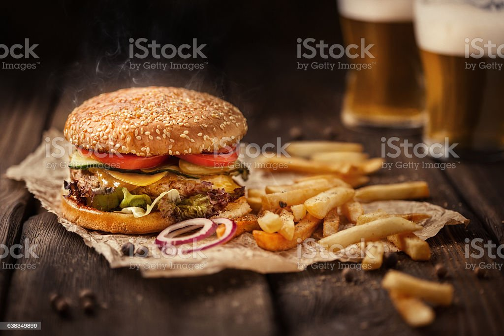 Tasty hamburger with french fries and beer on wooden table stock photo