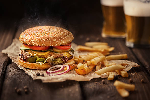 tasty hamburger with french fries and beer on wooden table - burger photos et images de collection
