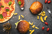 istock Tasty hamburger with french fries and pizza on table 1179655425