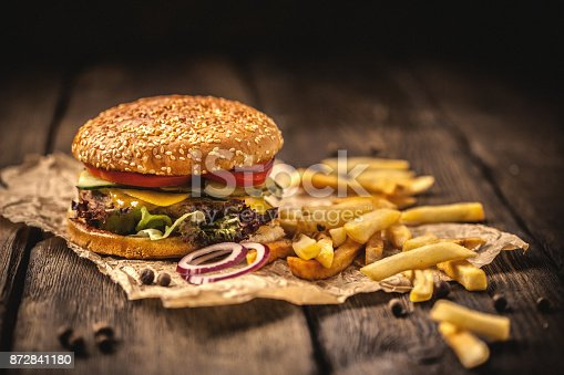 istock Tasty hamburger with french fries on wooden table 872841180