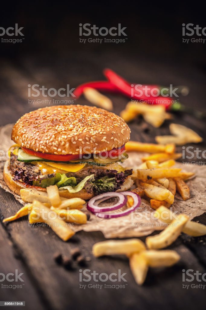 Tasty hamburger with french fries on wooden table stock photo