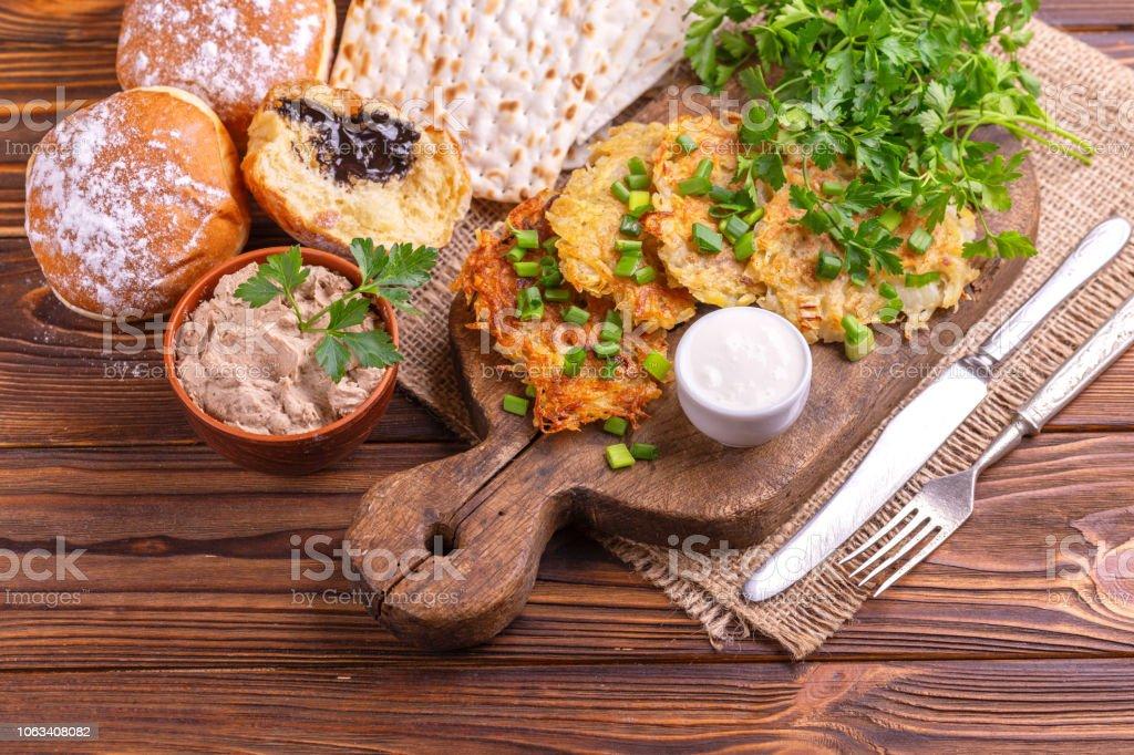 Chanukka-Feier lecker: hausgemachte traditionelle Kartoffel, knusprige Matzo, Leberpastete, süße Krapfen auf Vintage Schneidebrett – Foto