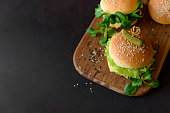 Tasty homemade burgers with lettuce, ketchup, cheese and chicken on brown wooden background. Copy space