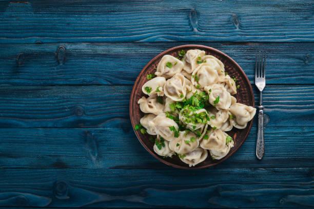 leckeren hausgemachten fleischklößchen vollkornmehl oder russischen pelmeni bestreut mit frischer petersilie auf platte auf holztisch, textfreiraum, ansicht von oben - knödel kochen stock-fotos und bilder