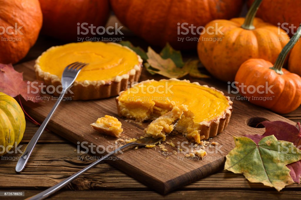 Tasty homemade pumpkin pies being eaten with forks on wooden board served with decorative pumpkins and marple leaves stock photo