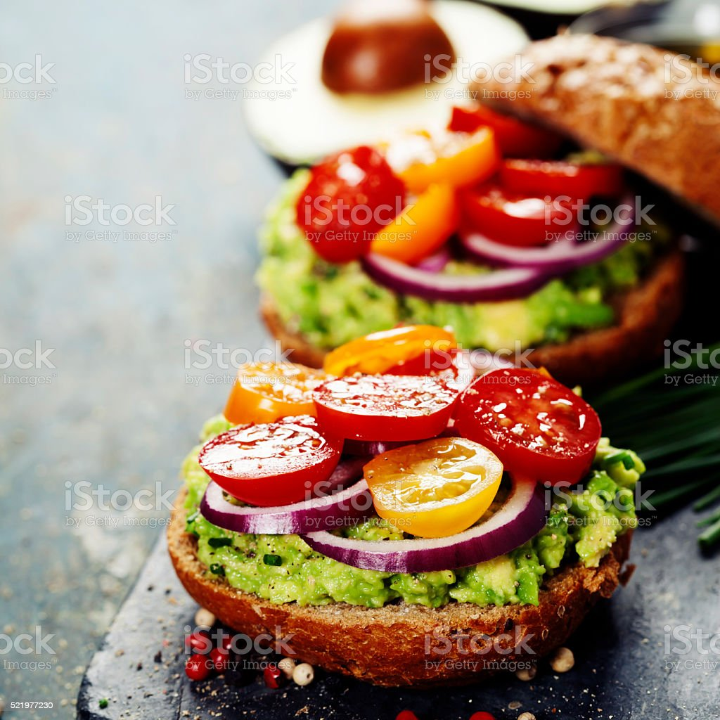 Tasty homemade sandwiches with avocado, tomato, onion and pepper stock photo