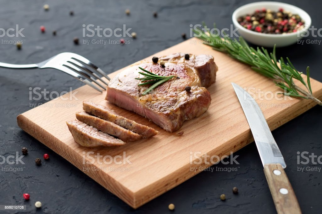 Tasty homemade well-done steak on wooden cutting board with fork and knife on stone background. stock photo