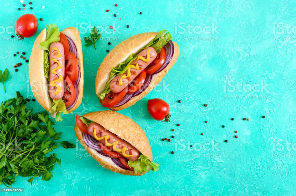 Tasty hot dogs on a bright background. Grilled sausage with tomatoes, red onions, lettuce, mustard in a crispy loaf. Street food. Fast food. The top view stock photo
