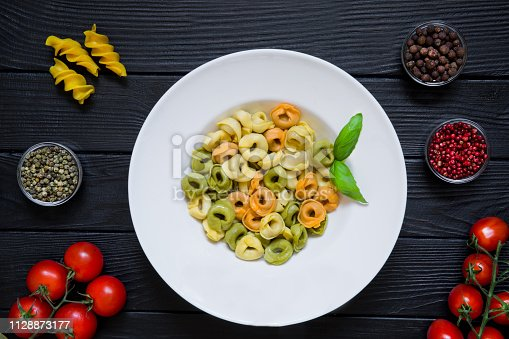 istock Tasty italian cuisine on black wooden table. Little tomatoes and different kinds of pepper. Natural healthy food. 1128873177