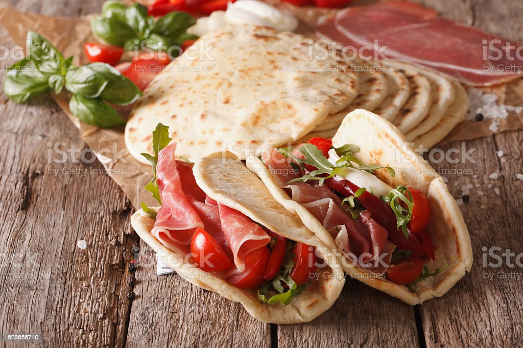 Tasty Italian piadina stuffed with ham, cheese and vegetables stock photo