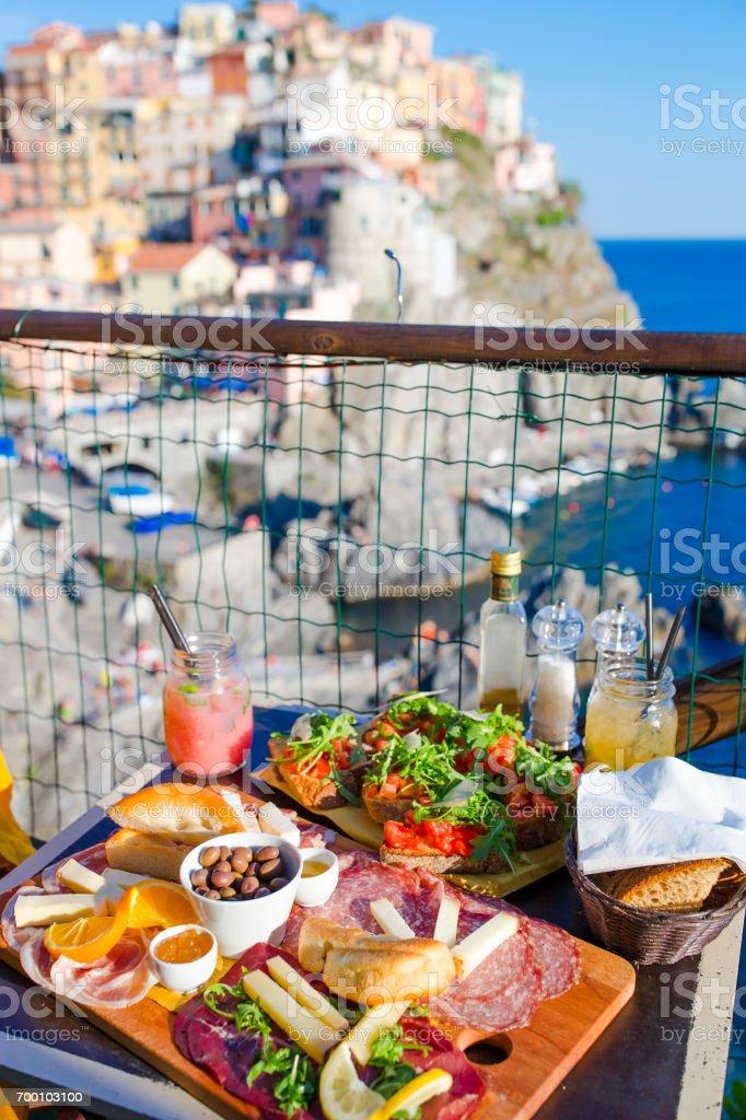 Leckere italienische Snacks. Frische Bruschettes, Käse und Fleisch auf dem Brett im Café im Freien mit Blick in Manarola, Italien – Foto