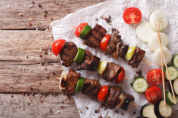 Tasty kebab with vegetables on skewers close-up. horizontal top view stock photo