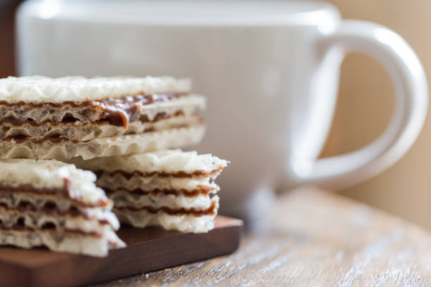 Tasty layered chcolate wafer with cup of coffeeon wooden table close-up stock photo
