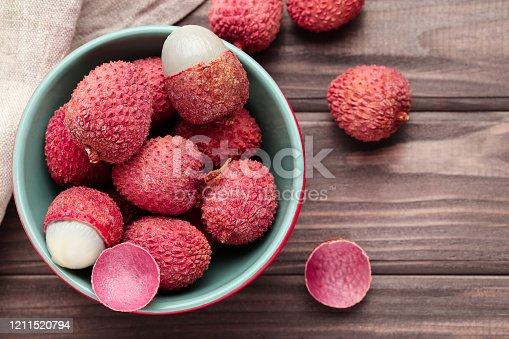 Tasty lychee in bowl on wooden table