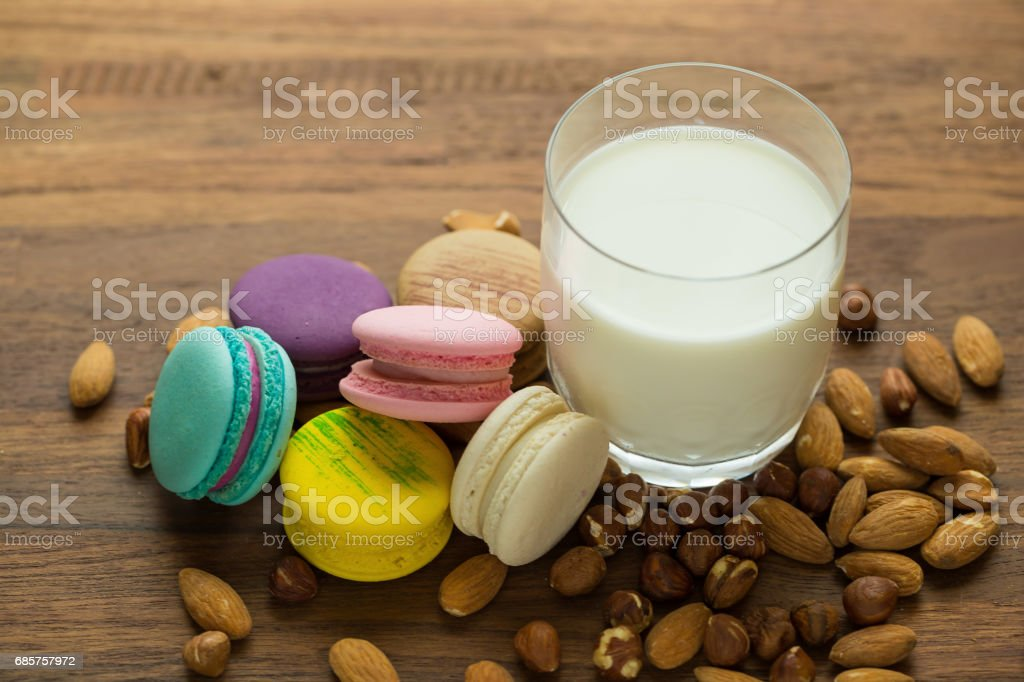 Tasty macaroons and cup of milk with almond on wooden background Selective focus. stock photo
