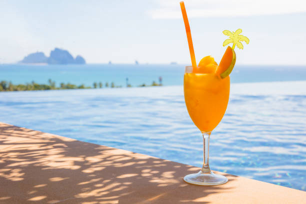 Tasty Mango Juice In Glass At Poolside stock photo