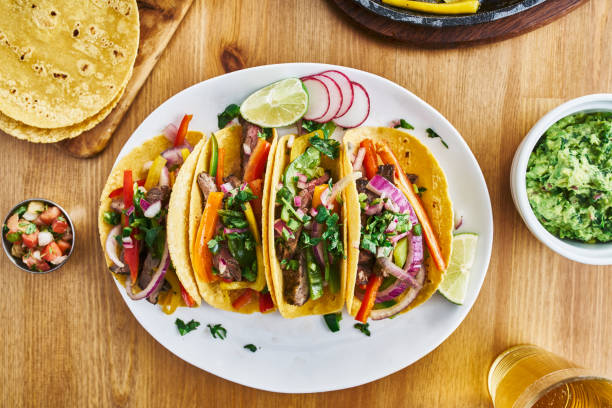tasty mexican tacos with beef fajita filling served with salsa tasty mexican tacos with beef fajita filling served with salsa and guacamole in flat lay composition taco stock pictures, royalty-free photos & images