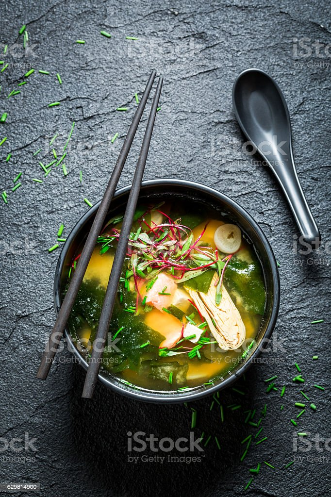 Tasty miso soup with salmon in black bowl stock photo
