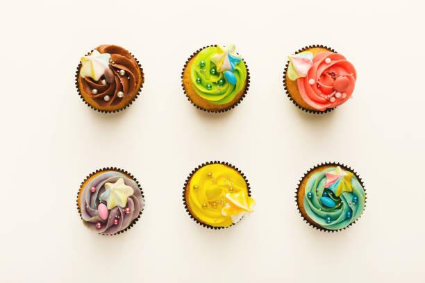 leckere muffins mit buttercreme isoliert auf weiss - vanille muffins stock-fotos und bilder