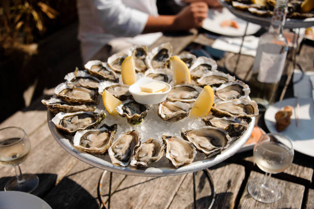 tasty oysters on the plate on the table - banchi di pesci foto e immagini stock