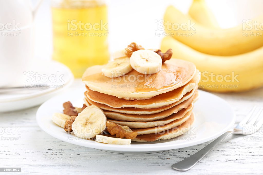 Tasty pancakes with banana and walnut on white wooden background stock photo