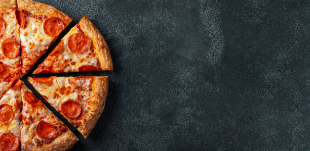 Tasty pepperoni pizza and cooking ingredients tomatoes basil on black concrete background. Top view of hot pepperoni pizza. With copy space for text. Flat lay. Banner Tasty pepperoni pizza and cooking ingredients tomatoes basil on black concrete background. Top view of hot pepperoni pizza. With copy space for text. Flat lay. Banner. pizza stock pictures, royalty-free photos & images
