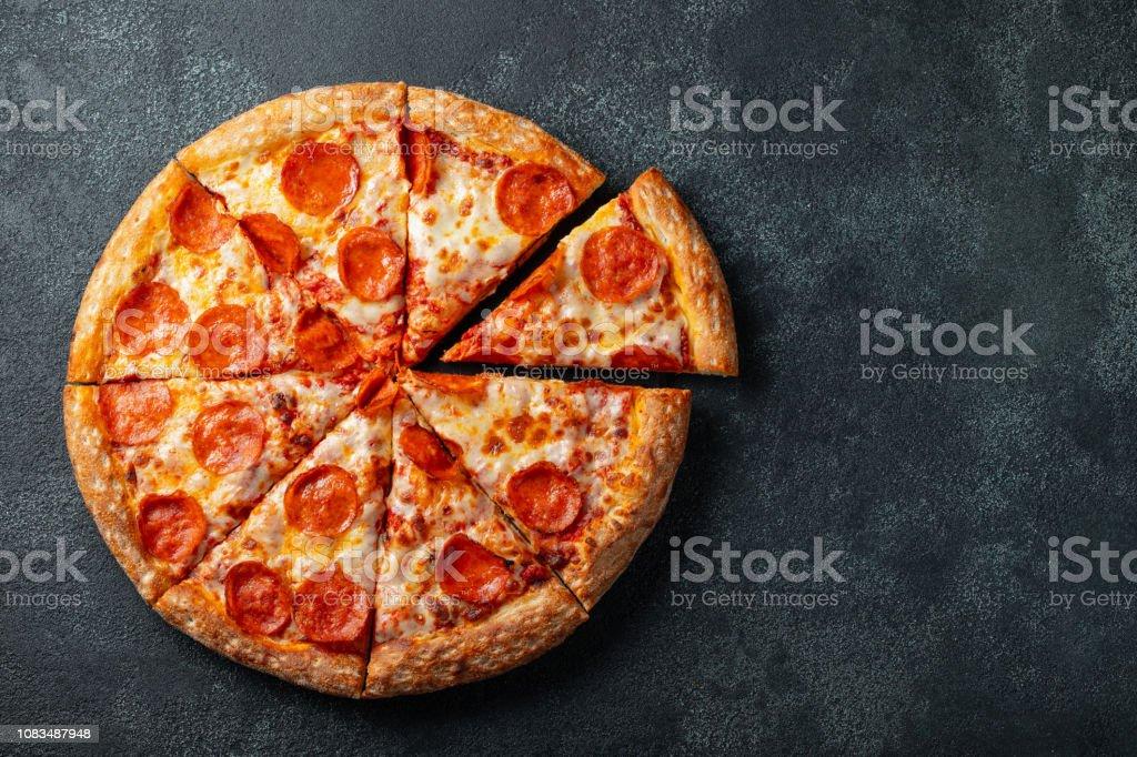 맛 있는 페 퍼로 니 피자와 블랙에 요리 재료 토마토 바 질 콘크리트 배경. 뜨거운 페퍼로니 피자의 최고 볼 수 있습니다. 와 텍스트 복사 공간. 평면 배치 - 로열티 프리 고기 스톡 사진