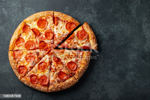 Tasty pepperoni pizza and cooking ingredients tomatoes basil on black concrete background. Top view of hot pepperoni pizza. With copy space for text. Flat lay.