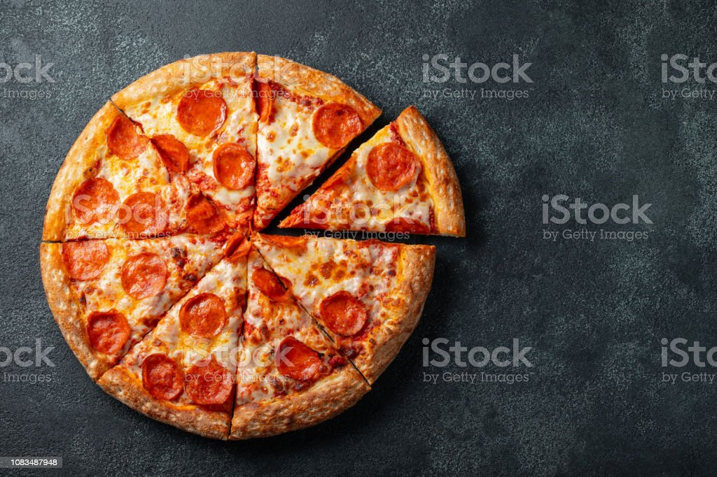 Tasty pepperoni pizza and cooking ingredients tomatoes basil on black concrete background. Top view of hot pepperoni pizza. With copy space for text. Flat lay stock photo