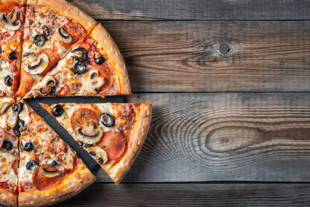 Tasty pepperoni pizza with mushrooms and olives. Tasty pepperoni pizza with mushrooms and olives on rustic wooden background. Top view of hot pepperoni pizza. With copy space for text. Flat lay. pizza stock pictures, royalty-free photos & images