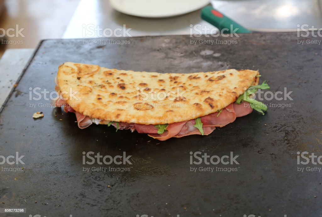 tasty piadina stuffed with ham and rocket on the hot plate to ba stock photo